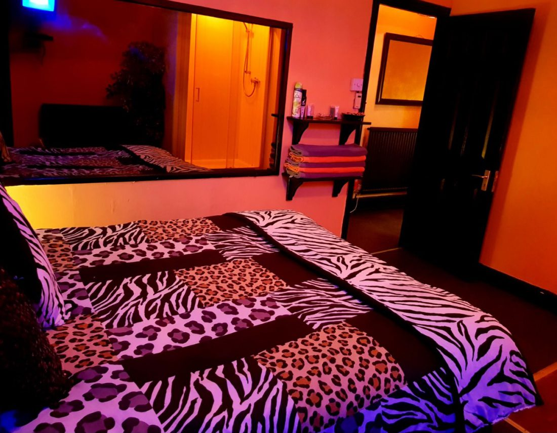Room with a double bed and subtle orange lighting
