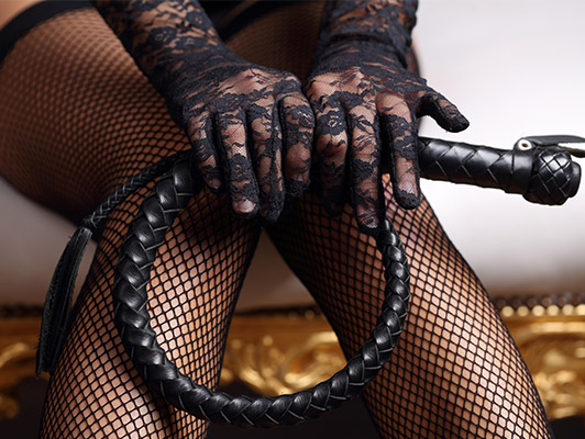 A lady in fishnets holding a whip